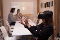 Female executive using virtual reality headset in office interior. — Stock Photo