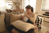Young mom sitting on sofa breastfeeding her baby in living room at home — Stock Photo