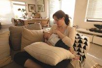 Jeune maman assise sur le canapé l'allaitement son bébé dans la salle de séjour à la maison — Photo de stock