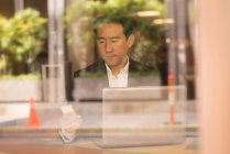 Asian businessman using mobile phone in cafe behind glass window — Stock Photo