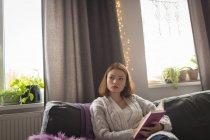 Femme réfléchie écrit sur un journal intime dans le salon à la maison — Photo de stock