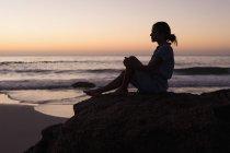 Силуэт женщины расслабляющий на скале в пляж на закате. — стоковое фото