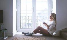 Mujer pensativa tomando café cerca de la ventana en casa - foto de stock