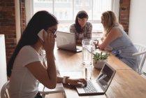 Руководители разговаривают по мобильному телефону, используя ноутбук, а коллеги обсуждают в фоновом режиме — стоковое фото