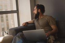 Homme regardant par la fenêtre tout en utilisant un ordinateur portable à la maison — Photo de stock