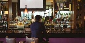 Vista posteriore dell'uomo d'affari che beve un bicchiere di whisky in hotel — Foto stock