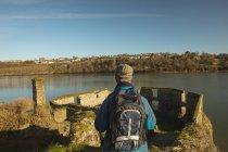 Вид сзади мужчин туристы с рюкзаком вблизи озера в сельской местности — стоковое фото