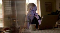 Femme mûre réfléchie utilisant un ordinateur portable à la maison — Photo de stock