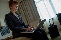 Mujer de negocios usando el ordenador portátil en la cama en la habitación de hotel - foto de stock