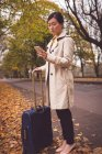 Businesswoman using mobile phone in street during autumn — Stock Photo