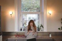 Jovem mulher usando telefone celular em casa — Fotografia de Stock