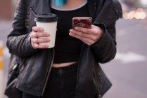 Donna che utilizza il telefono cellulare mentre prende un caffè in strada — Foto stock