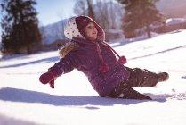 Fille insouciante jouer dans la neige pendant l'hiver — Photo de stock