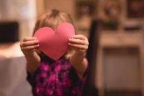 Menina segurando coração forma decoração em casa — Fotografia de Stock