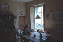 Junge Frau benutzt Handy zu Hause — Stockfoto