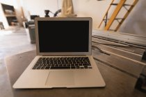 Close-up of laptop on table in industrial workshop. — Stock Photo