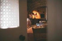 Жінка, використовуючи ноутбук під час в будинку маючи сніданок — стокове фото