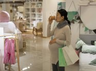 Pregnant woman having coffee in store — Stock Photo