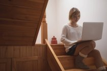 Woman using laptop on wooden staircase at home — Stock Photo