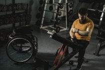 Handicapped man using mobile phone on bench press in gym — Stock Photo