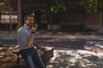 Man talking on mobile phone near street on a sunny day — Stock Photo