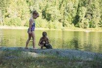 Брат грати з бруду неподалік riverbank сонячний день — стокове фото