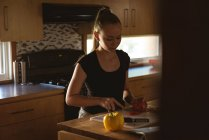 Girl standing in kitchen and cutting tomato with knife at home. — Stock Photo