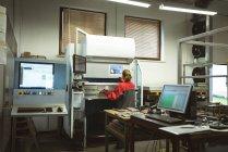 Жіночий працівник перевірки машини заводі — стокове фото