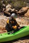 Femme debout avec bateau kayak de rivière qui coule l'eau. — Photo de stock