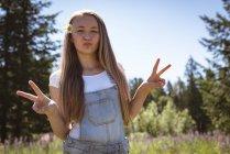 Retrato de chica mostrando signo v en el campo en verano . - foto de stock
