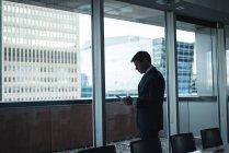 Geschäftsmann mit Handy im Konferenzraum — Stockfoto