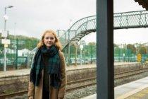Портрет жінку, що стоїть на залізничному вокзалі — стокове фото