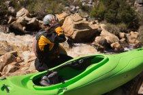 Femme assise avec bateau kayak sur les rochers au bord de rivière. — Photo de stock