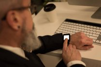 Business executive using smartwatch at desk in office — Stock Photo