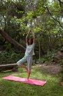 Mujer practicando yoga en el jardín en un día soleado - foto de stock