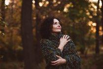Sonriente mujer madura de pie en el bosque - foto de stock