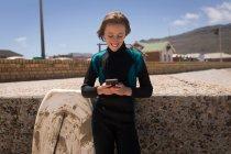 Дівчинка-підліток у гідрокостюм використання мобільного телефону на кожному — стокове фото