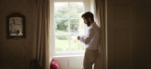 Hombre revisando su reloj cerca de la ventana en casa - foto de stock