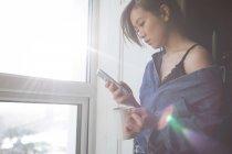 Femme buvant café lors de l'utilisation de téléphone portable à la maison — Photo de stock