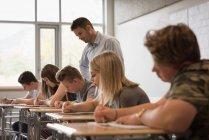 Profesora asistiendo a estudiantes universitarios en sus estudios en el aula - foto de stock