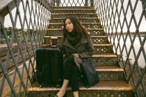 Thoughtful woman sitting on staircase at railway station — Stock Photo