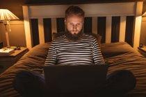 Человек сидит на кровати в темной комнате, используя свой ноутбук дома — стоковое фото