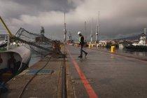 Side view of dock worker walking in the shipyard — Stock Photo