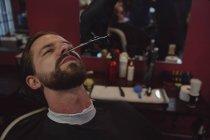 Uomo che si fa tagliare la barba con le forbici dal barbiere — Foto stock