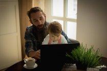 Père ayant café tandis que fils jouer sur ordinateur portable à la maison — Photo de stock