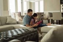 Father and daughter using digital tablet at home — Stock Photo
