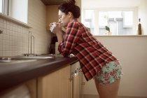 Femme buvant du café dans la cuisine à la maison . — Photo de stock