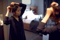 Женщина готовится перед зеркалом в отеле — стоковое фото