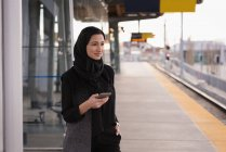Mulher no hijab usando telefone celular na estação ferroviária — Fotografia de Stock
