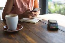 Section médiane d'adolescente à l'aide de téléphone portable à côté du terminal de paiement au restaurant — Photo de stock